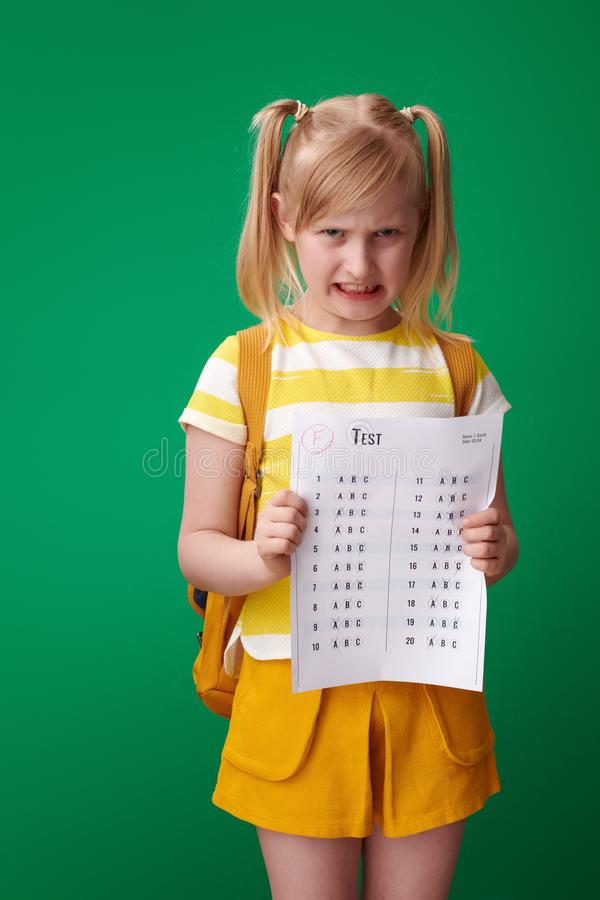 Angry pupil received bad grade against green background. Angry pupil with backpack received a bad grade against green background stock photography