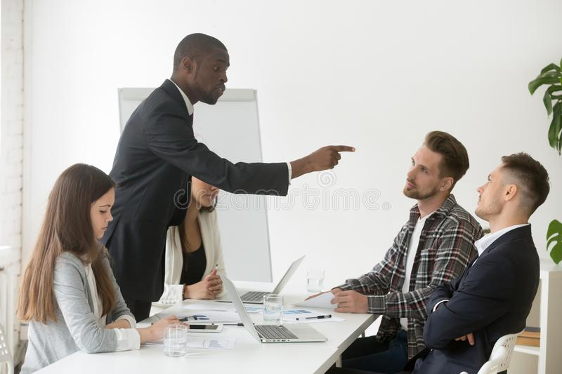 Angry rude african businessman pointing finger threatens colleag. Angry rude african businessman pointing finger threatens caucasian colleague at team meeting stock image