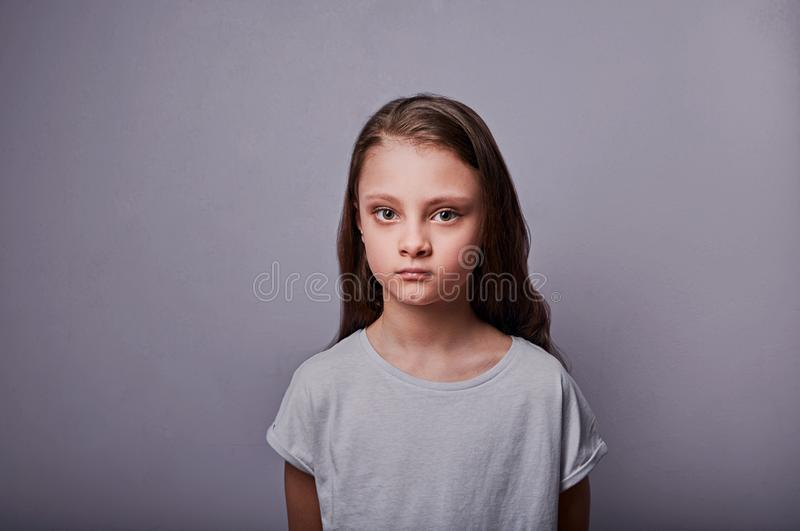 Angry sad kid girl with serious emotions looking on dark background with empty copy space royalty free stock image
