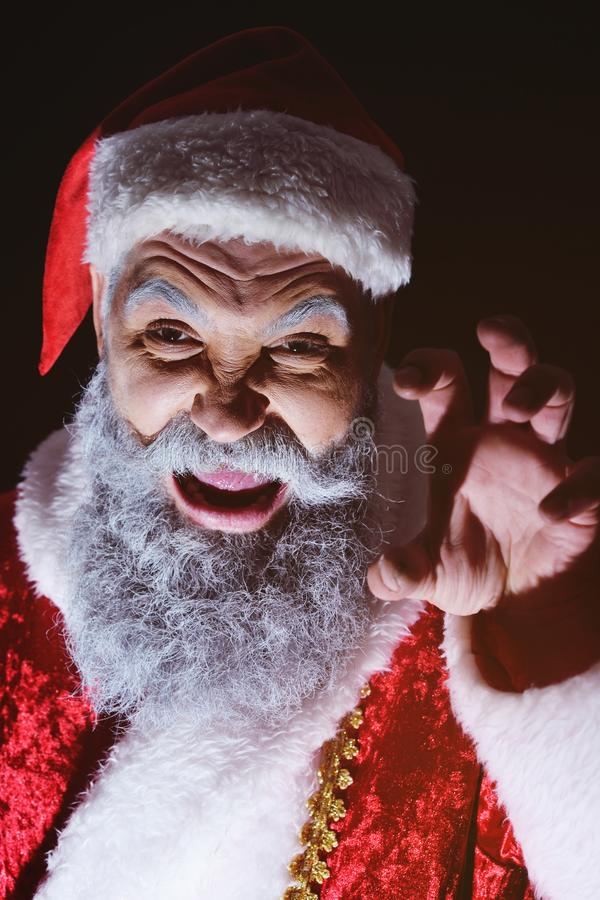 Santa furiously grimaces against a dark background. Angry Santa furiously grimaces against a dark background royalty free stock photo