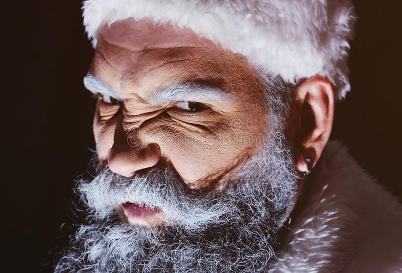Angry Santa furiously grimaces. Against a dark background stock photos