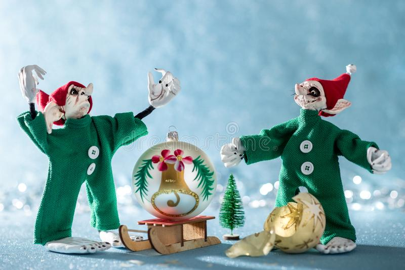 Angry Santas Helper Elf With Raised Hands Standing Next to Second Elf That Broke a Christmas Bauble. North Pole Christmas Scene. stock photography