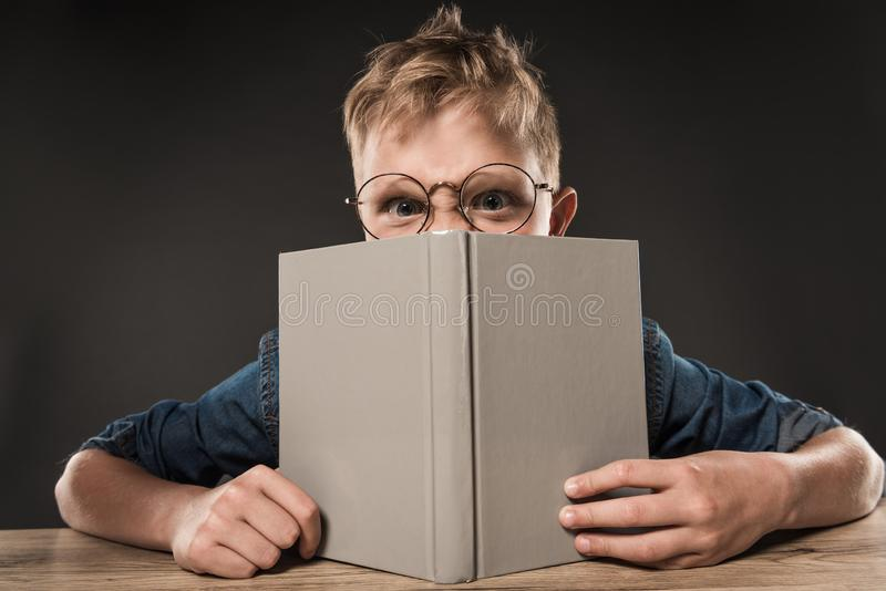 Angry schoolboy in eyeglasses covering face by book at table on grey. Background royalty free stock image