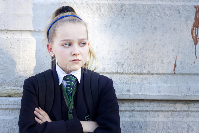 Angry schoolgirl. Teenage kid in school uniform looking angry, standing against a concrete wall with graffiti. Real people, candid shot stock photos