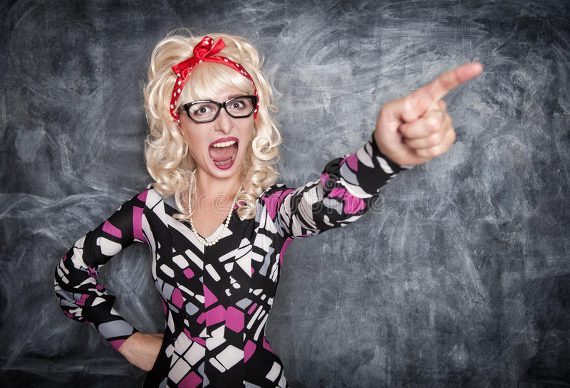 Angry screaming retro teacher pointing out. On chalkboard blackboard background stock images