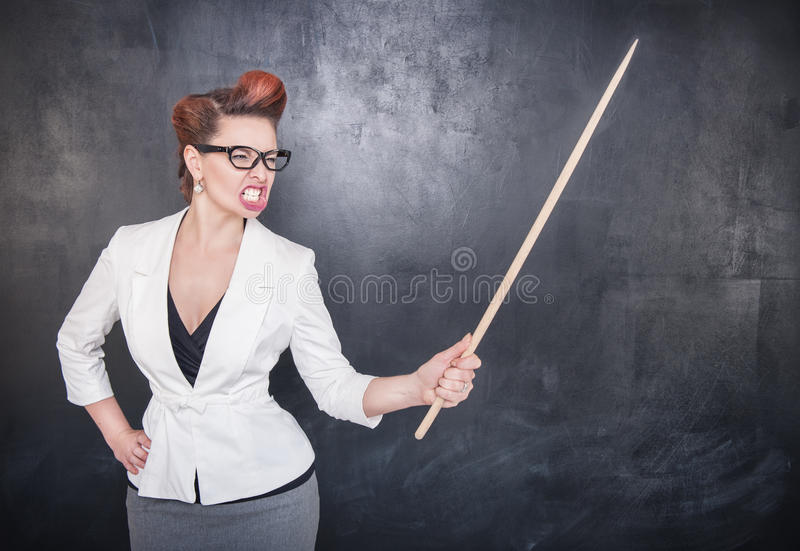 Angry screaming teacher with pointer on blackboard background stock photos