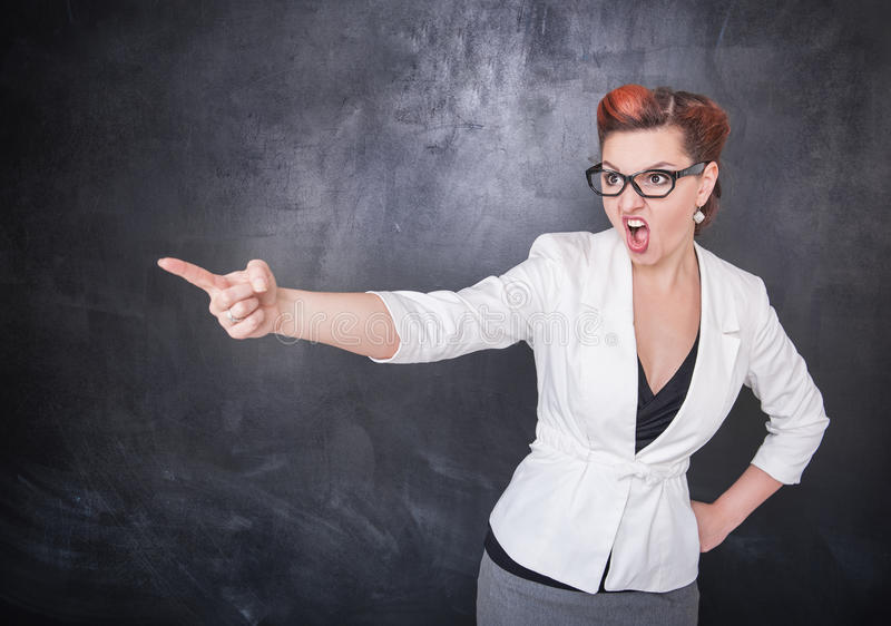 Angry screaming teacher pointing out on blackboard background royalty free stock images