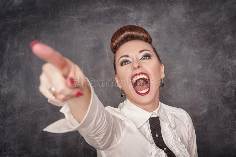 Angry screaming woman in white blouse pointing out. On the chalkboard background royalty free stock photos