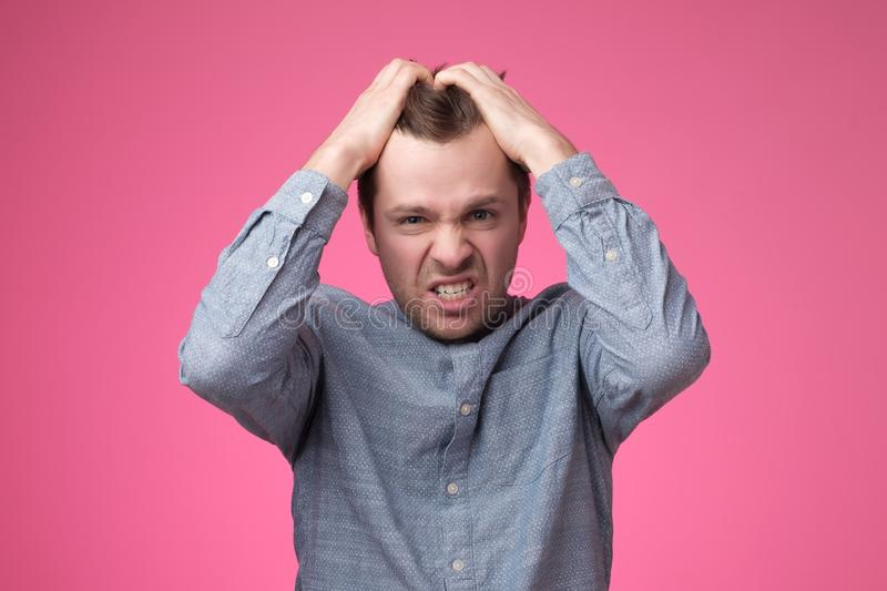 Angry screaming young man putting hands on head on pink wall in studio. royalty free stock image