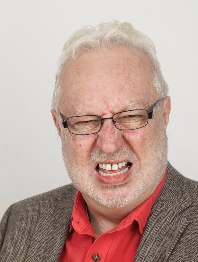 Angry senior bares his teeth. Angry senior with glasses bares his teeth - on bright background royalty free stock image