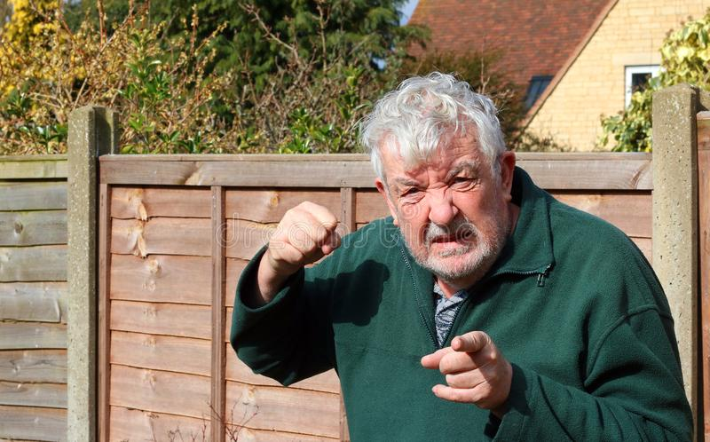 Angry senior man raised fist. Pointing. An angry senior man looking towards the camera and pointing. Staring at camera in a threatening manner. Ready to strike stock photo