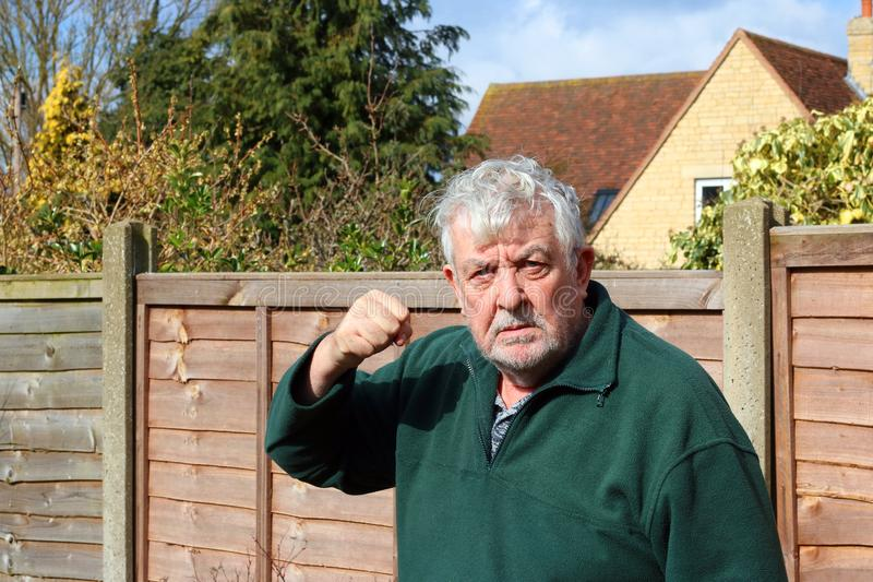 Angry senior man raised fist. Ready to punch. An angry senior man looking towards the camera and shaking his raised fist. Staring at camera in a threatening stock image