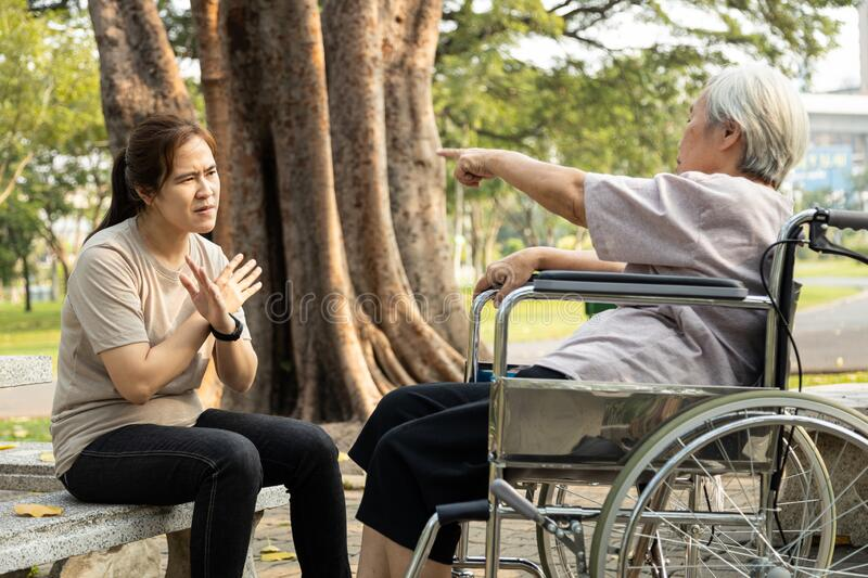 Angry senior person in wheelchair has quarrel violently with aggressive caregiver woman at outdoor nursing home,female elderly royalty free stock image