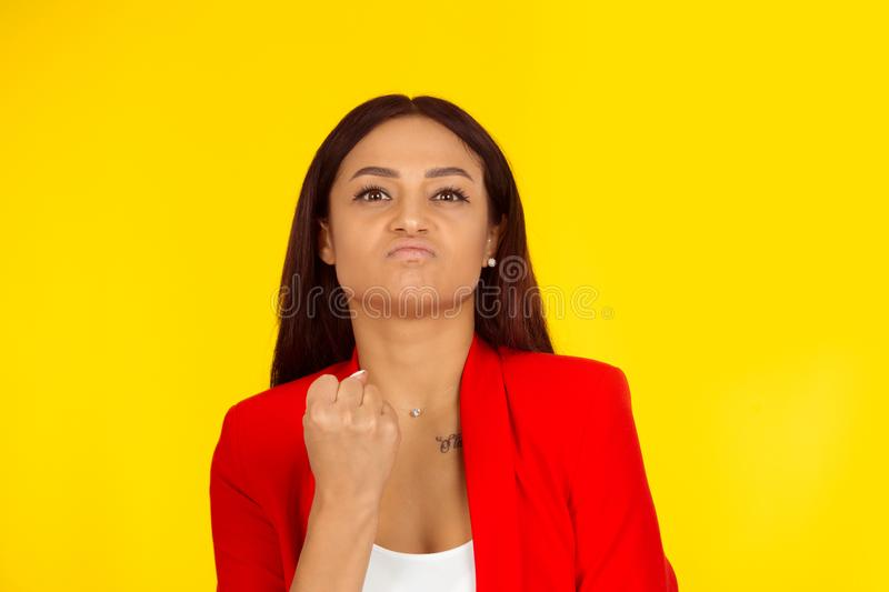 Angry serious woman looking at camera, clenching fist, demonstrating power royalty free stock photo