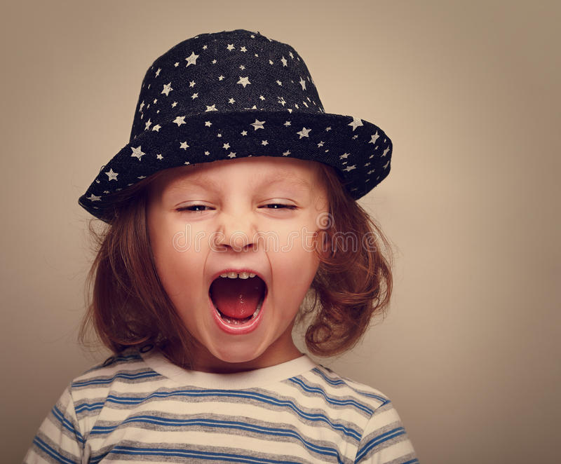 Angry shouting kid girl with open mouth. Closeup vintage stock images