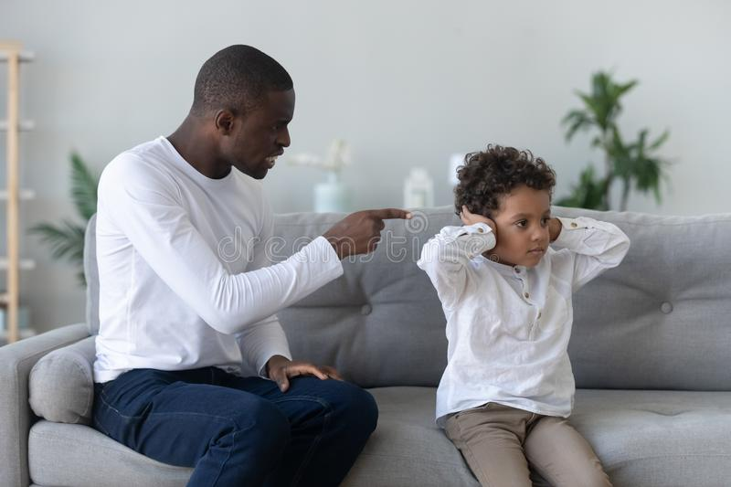 Angry single black father scolding stubborn fussy little african son. Closing ears not listening ignoring dad punish small mixed race kid boy for bad behavior stock photography
