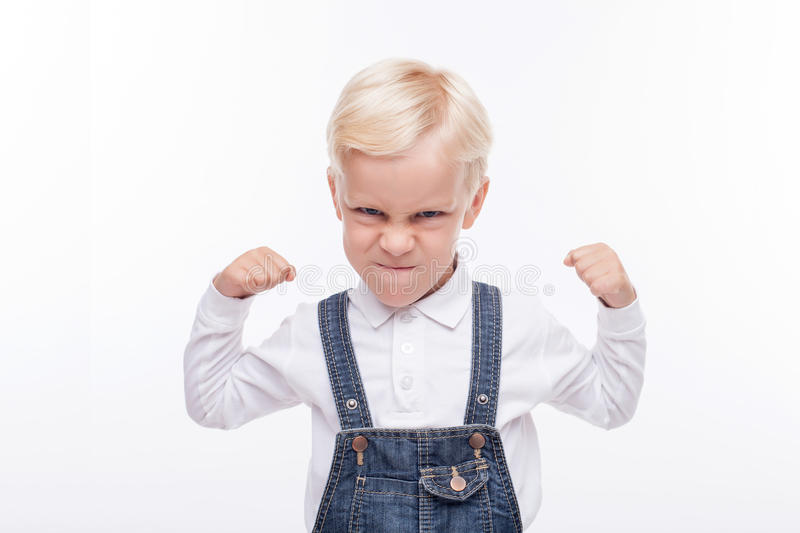 Angry small boy is ready to fight. Cheerful male child is standing and preparing his fists for fighting. He is looking forward with aggression. Isolated and copy stock photography