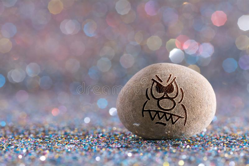 The angry stone emoji. Emotions on color glitter boke background stock photos