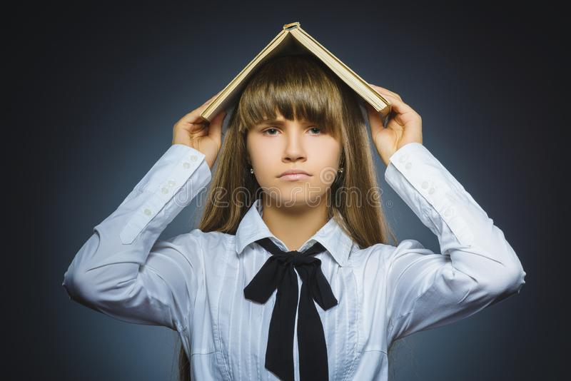Angry or stressed girl with book. child on grey background. studies concept. Angry or stressed girl with book. Closeup Portrait of handsome teen on grey stock photography