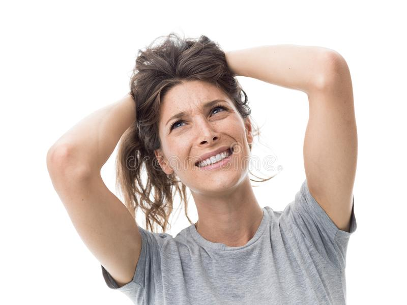 Angry woman having a bad hair day. Angry stressed woman having a bad hair day, she is holding her messy and tangled hair stock photography