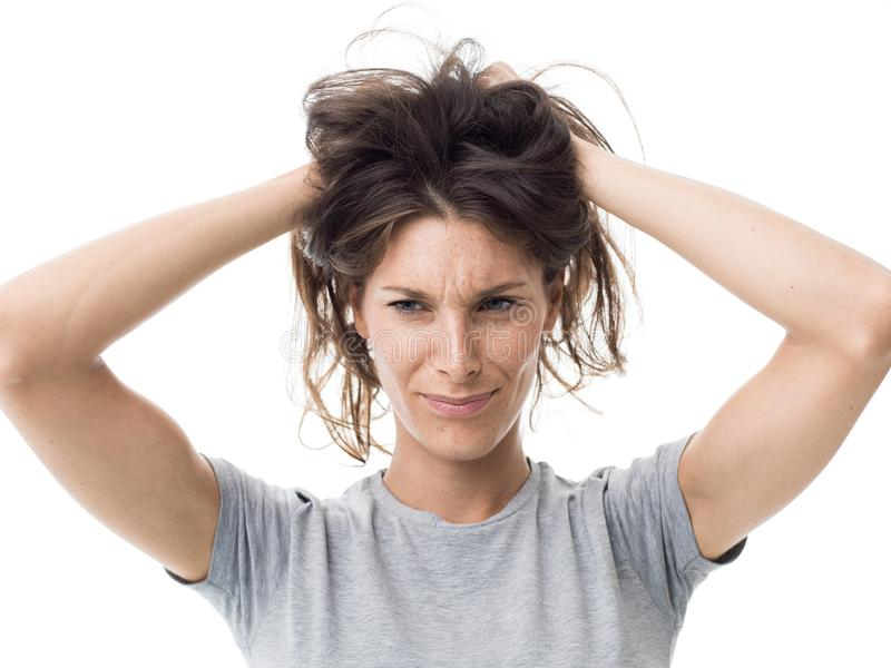 Angry woman having a bad hair day. Angry stressed woman having a bad hair day, she is holding her messy and tangled hair royalty free stock images