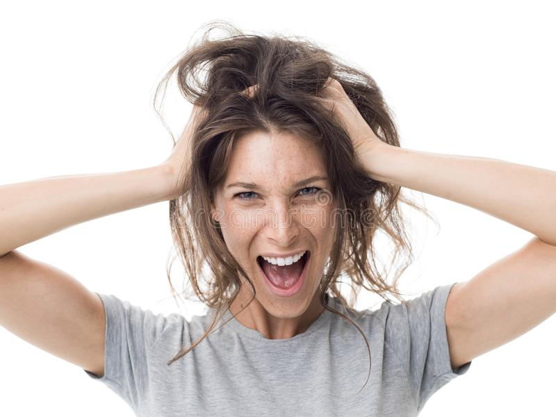 Angry woman having a bad hair day. Angry stressed woman shouting and having a bad hair day, her hair is messy and tangled royalty free stock photo
