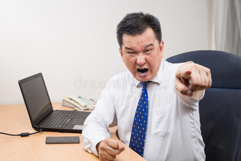 Angry and stressful Asian manager shouting and pointing in office stock photography