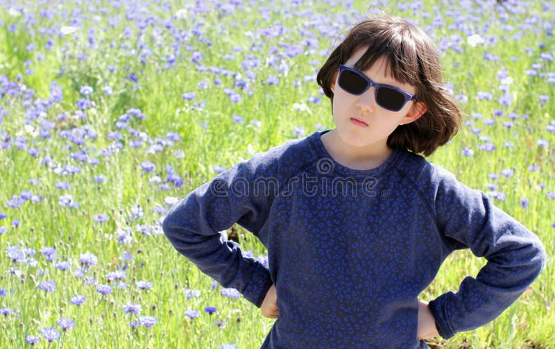 Angry sulking boyish child standing for responsibility statement, beautiful meadow. Angry sulking boyish child standing with concerned hands on hips for royalty free stock photos