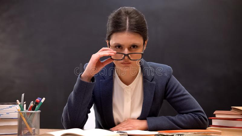 Angry teacher looking aggressively to camera taking off glasses, strict lecturer stock photos
