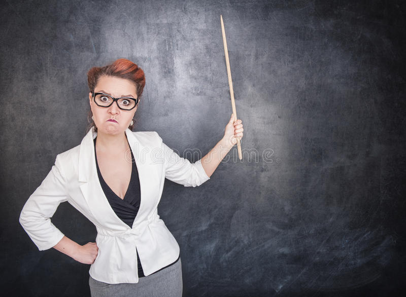 Angry teacher with pointer. On the chalkboard blackboard background royalty free stock images