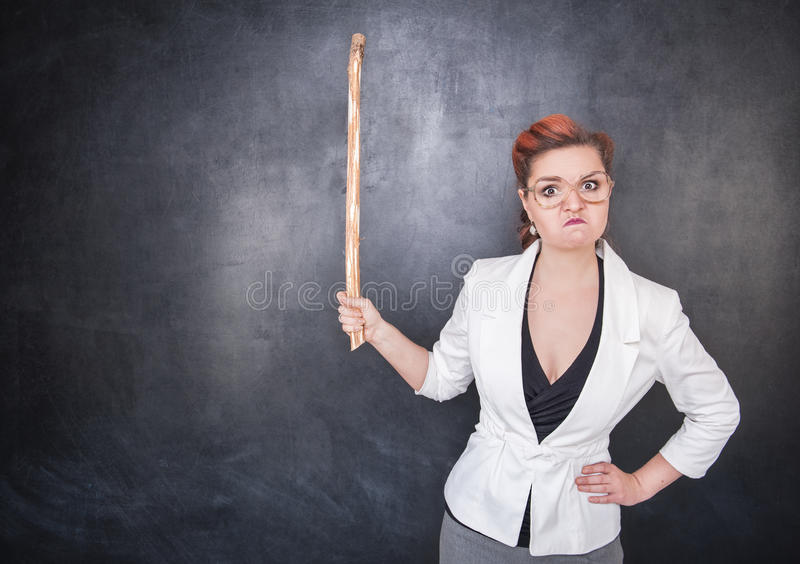 Angry teacher with pointer. On the chalkboard blackboard background royalty free stock photo