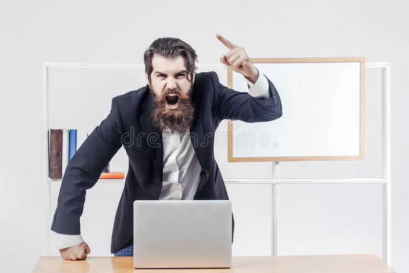 Angry teacher or professor in black suit shouts raised his finger up standing near desk with laptop. Angry teacher or professor in black suit shouts raised his stock photo
