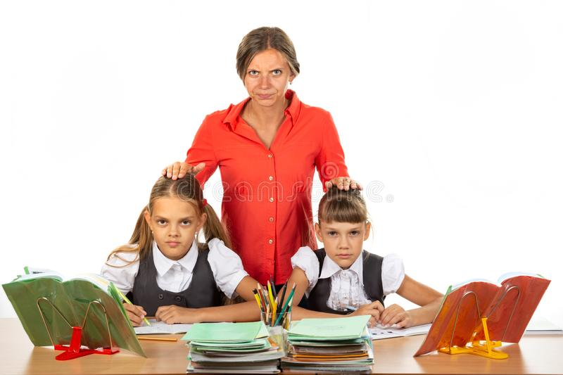 Angry teacher stands behind students sitting at her desk and puts her hands on the heads of children stock photography