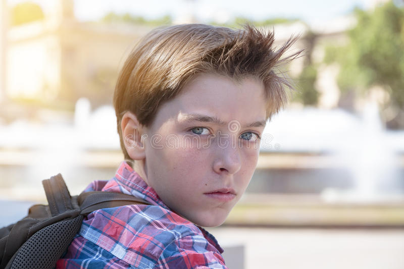 Angry teenage boy with backpack stock photo
