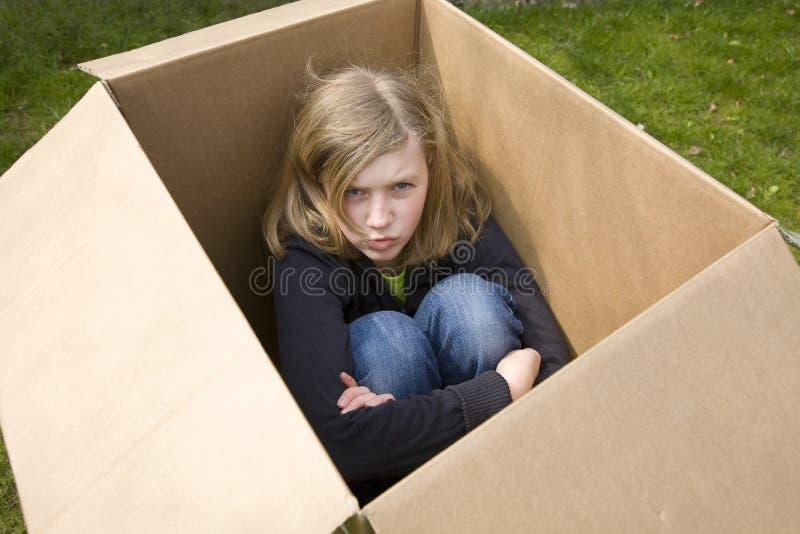 Angry teenage girl sitting in a cardboard box stock photos