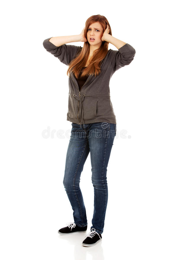 Angry teenage woman covering ears with hands stock image
