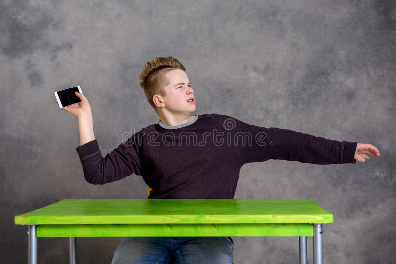 Angry teenager with smartphone. In front of gray background royalty free stock images