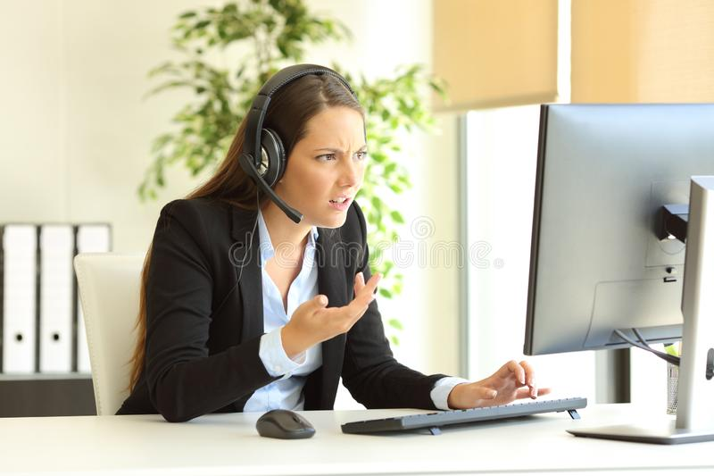 Angry tele marketer attending customer at office stock photo