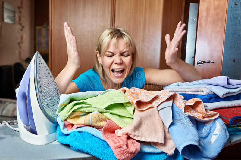 Angry and tired woman housewife from ironing board stock image