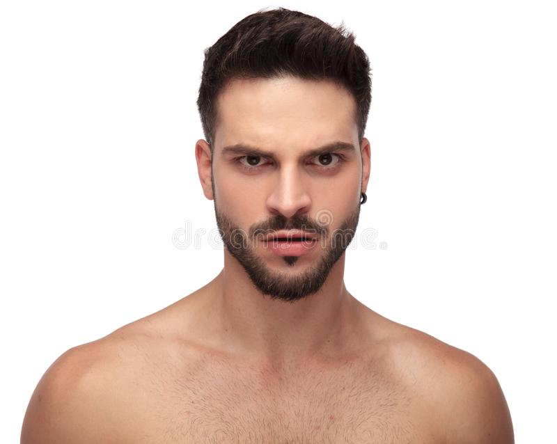 Angry undressed guy looking upset with eyebrow up. On white background stock image