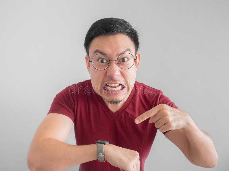 Angry and unpleasant face of man is looking at his watch waiting royalty free stock images