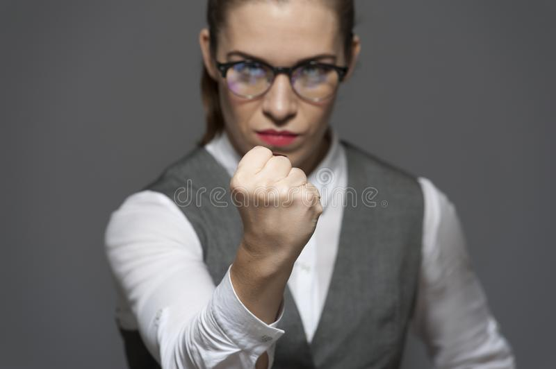 Angry unpleased attractive businesswoman looking at the camera showing fist. Wearing eyeglasses dressed in blouse with jacket on grey background royalty free stock images