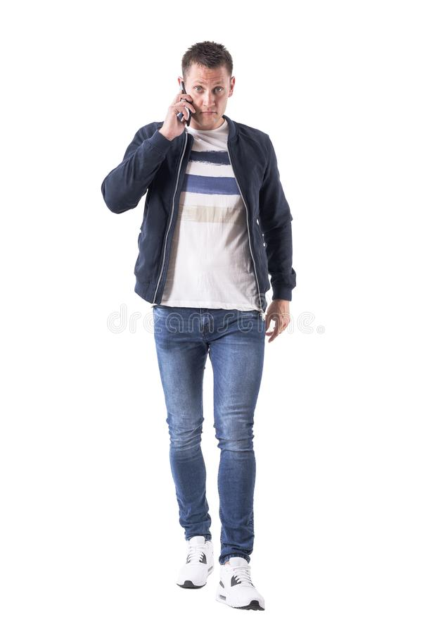 Angry upset adult man talking on the phone looking at camera walking and approaching. Full body isolated on white background royalty free stock image