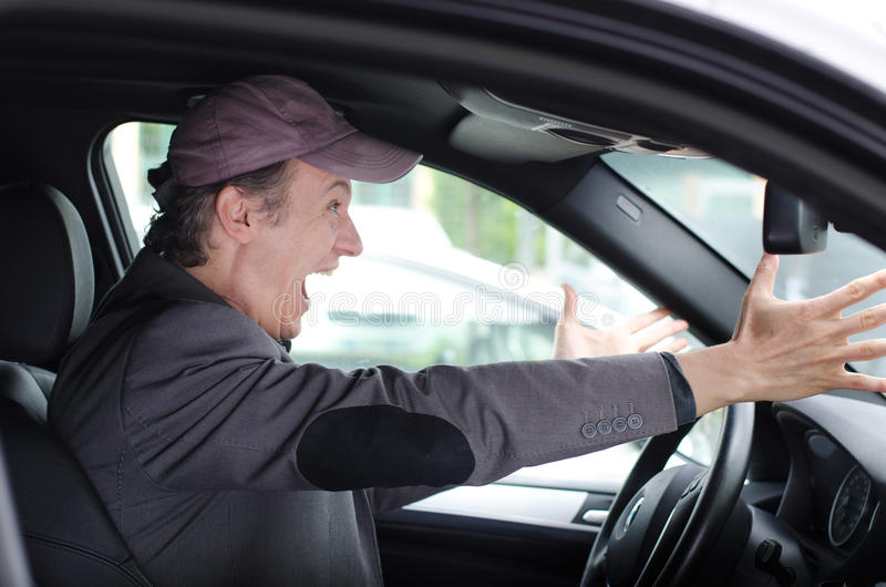 Angry upset man at wheel driving his car screaming stock images