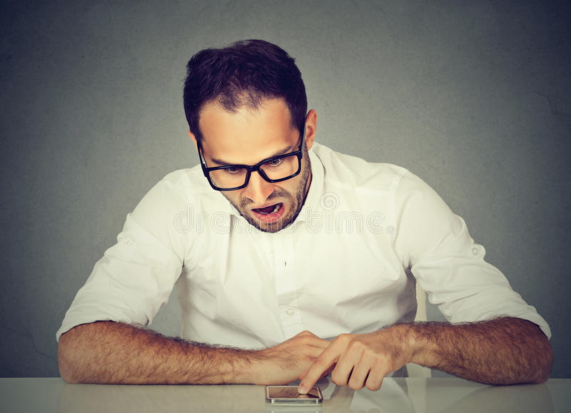 Angry upset young man using his smartphone stock photos