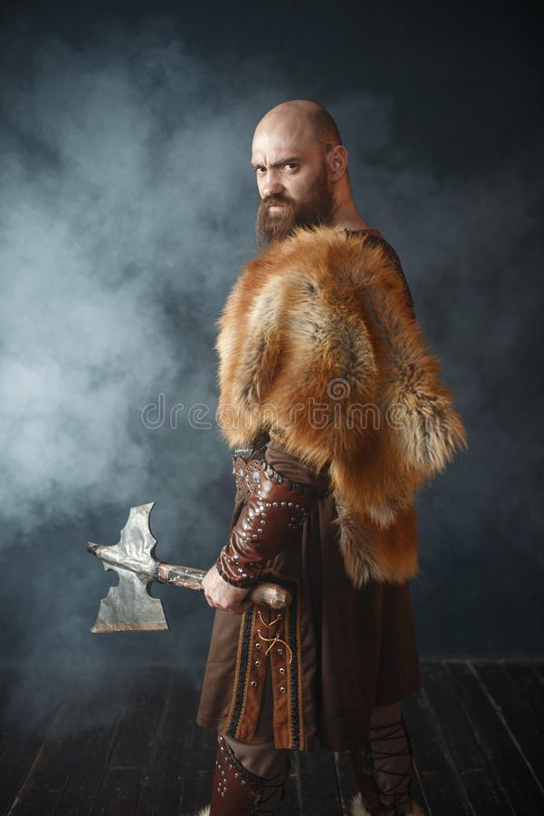 Angry viking with axe, martial spirit, barbarian. Image. Ancient warrior in smoke stock images