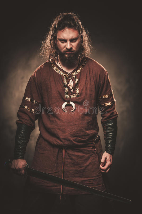 Free Angry Viking With Sword In A Traditional Warrior Clothes, Posing On A Dark Background. Royalty Free Stock Images - 76144189