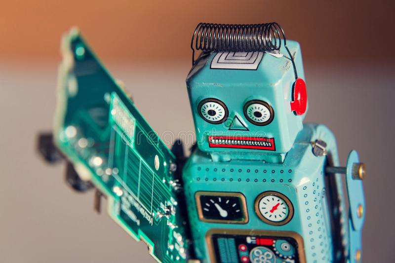 Tin toy robot carries computer circuit board, artificial intelligence concept stock image