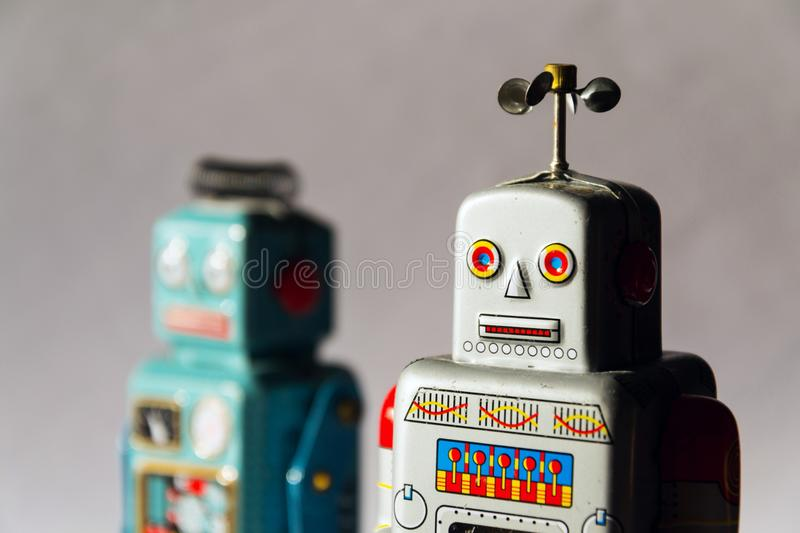 Angry vintage tin toy robots, artificial intelligence, robotic delivery concept stock photography