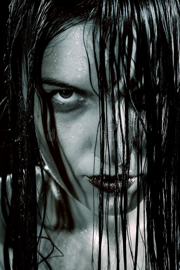 Angry wet woman. Serious angry woman with wet black hair looking at camera stock image